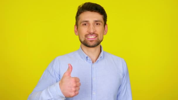 Young man in light blue shirt is smiling and shows thumb up, like.