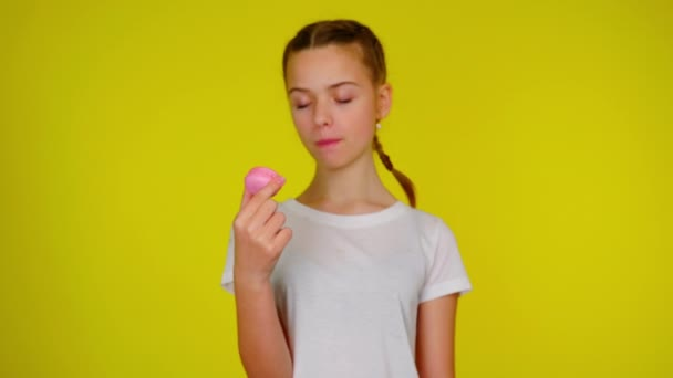 Teenage girl in a white T-shirt shows a pink macaroon and smiles