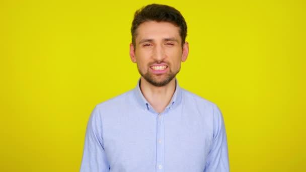 Rozzlobený mladý muž v světle modré košili se zubí zuby.
