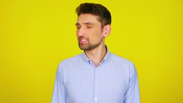 Mladý muž v světle modré košili se usmívá a mrká