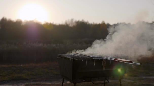 Klobásy se vaří v kouři na grilu na pozadí západu slunce