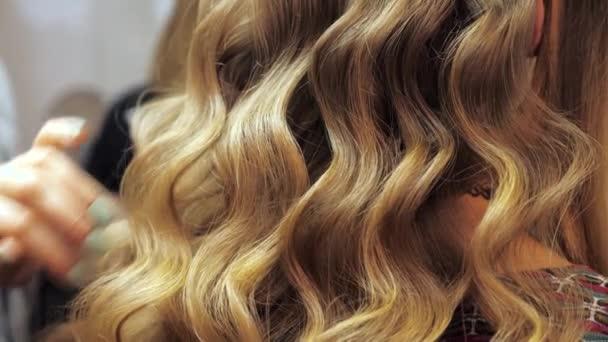 Zblízka profesionální kadeřník narovnává ženské vlasy