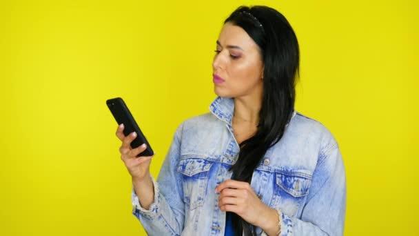 Frau benutzt Smartphone, dann ist sie überrascht und sagt wow auf gelbem Hintergrund