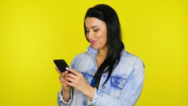 Žena drží smartphone v rukou, píše zprávu do poslíčka a usmívá se