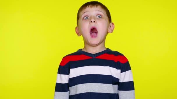 Kleiner Junge im bunten Pullover überrascht auf gelbem Hintergrund