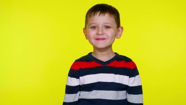 Zmatené dítě se rozhlédne a usměje se na žlutém pozadí s kopírovacím prostorem