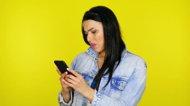 Empörte Frau hält Smartphone in der Hand und schreibt Nachricht im Messenger