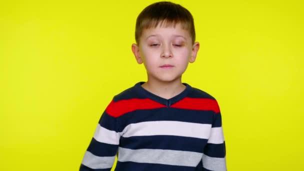 Kleiner Junge überrascht, wenn er den Mund mit Handfläche auf gelbem Hintergrund schließt