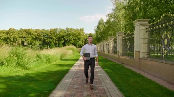 Businessman with a laptop in his hand walks through the park and looks around