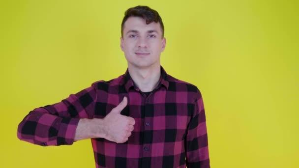 Muž v růžové kostkované košili se usmívá, zvedne ruku a ukazuje jako na žlutém pozadí
