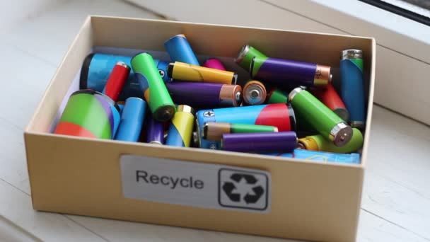 Battery Collection Box. Waste sorting. Young man places used batteries into the box