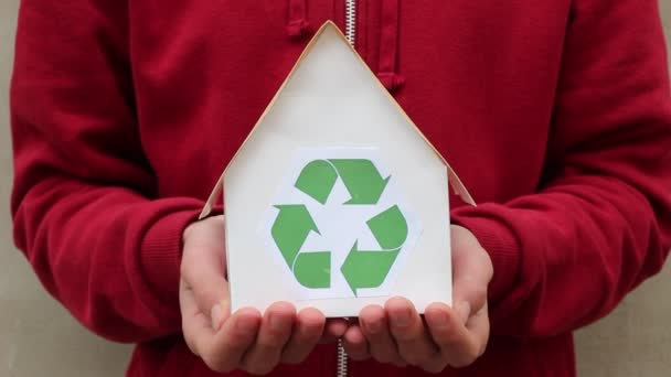 Hands of young man holding paper house with recycling symbol. People, ecology, environment and conservation concept - close up of hands holding house with green recycling sign