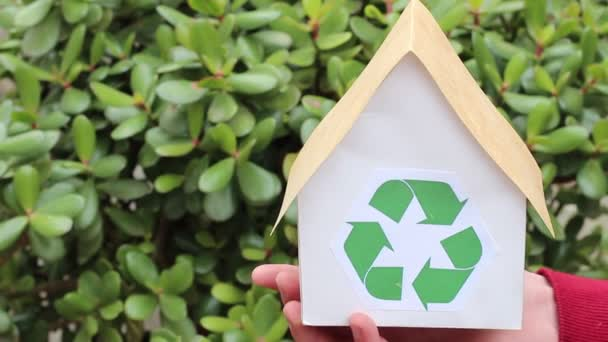 Hands Holding House With Green Recycling Sign. People, ecology, environment and conservation concept - close up of hands holding house with green recycling sign