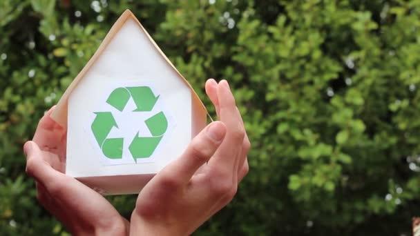Ház újrahasznosítás jel. Emberek, ökológia, környezet- és természetvédelmi koncepció - közelről a kezei ház zöld újrahasznosítás jel