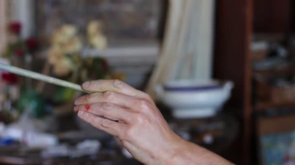 Ruka s detailním umělcova štětce. Umělec maluje v olejomalba Studio