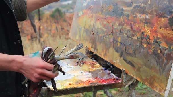 Profesionální umělec maluje obraz na plátně pomocí olejových barev. Krajina olejomalba. Podzimní vinice. Moře. Hory
