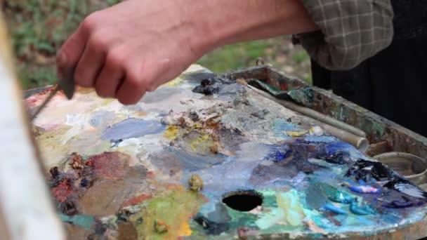 Profesionální umělec maluje obraz na plátně pomocí olejových barev. Umělcova paleta detail. Míchání olejové barvy