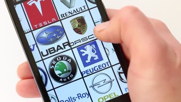 Logos of automobile manufacturers on smartphone screen. Maserati, Mazda, Mercedes-Benz, Mini, Nissan, Opel, Peugeot, Porsche, Renault, Rolls-Royce, Skoda, Subaru, Tesla, Toyota, Volkswagen, Volvo