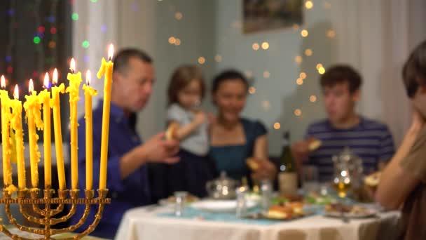 Veselá židovská rodina slaví svátky Chanuky. Chanuka svítí doma, s rodinou a přáteli. Večeře u Chanuky a jídlo. Menora s devíti hořícími svíčkami v popředí
