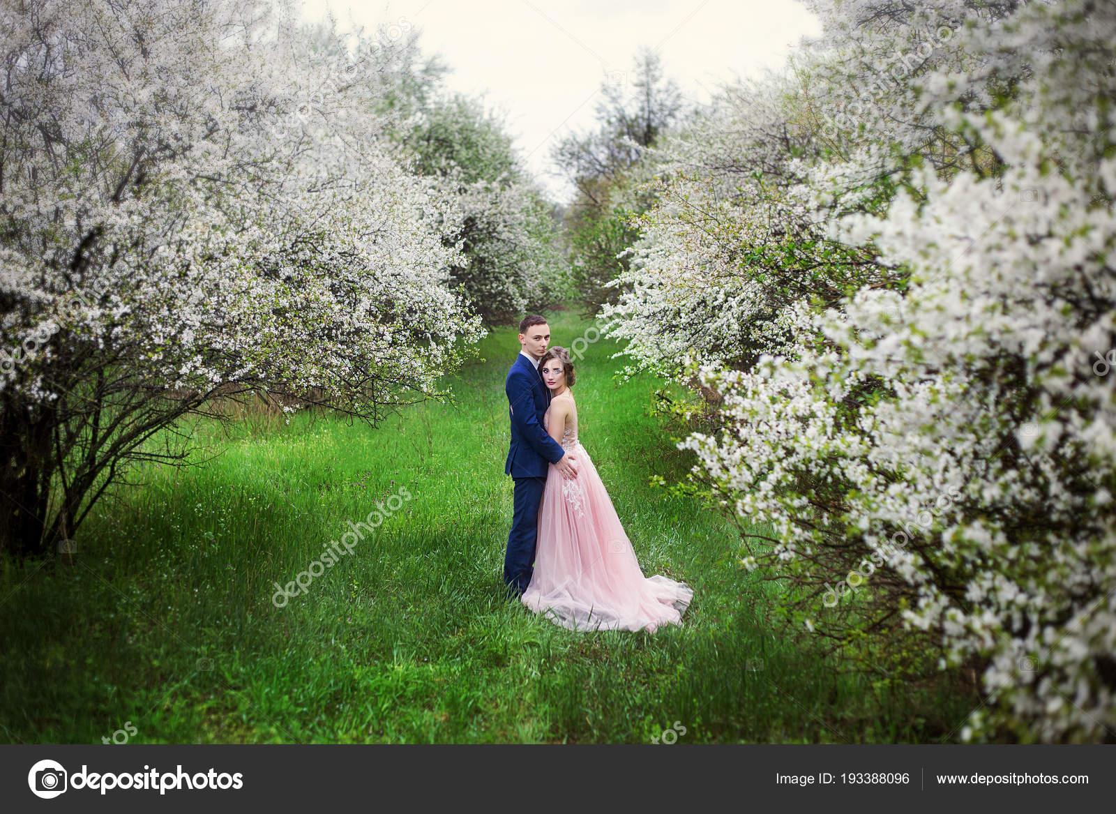 Bella coppia innamorati wedding dresses contro sfondo giardini fiore