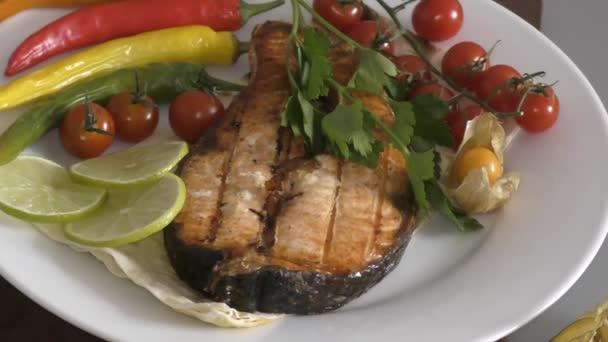 Ryb losos na grilu s čerstvými bylinkami a zeleninou