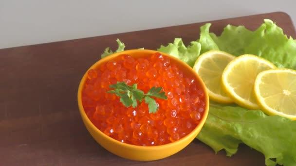Roter Kaviar und frisches Grünzeug am Schneidebrett