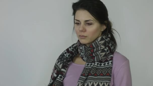 Ill girl with runny nose in scarf with temperature coughs in front of white background
