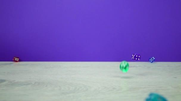 Zpomalený záběr různobarevné kostky padají na purplebackground