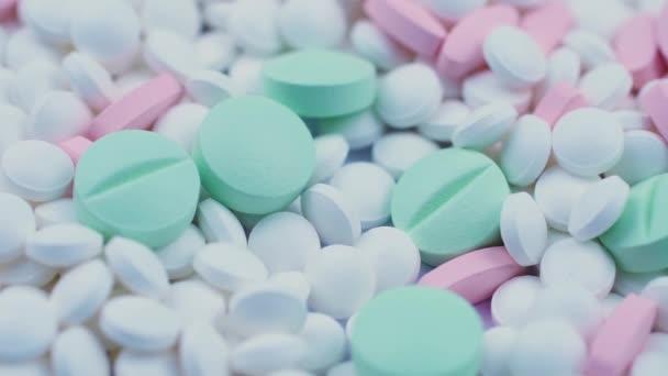 Kulaté zelené a růžové léky spočívají s bílými antivirovými pilulkami. Rotace