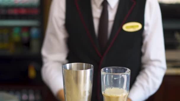Der Barkeeper macht einen alkoholischen Cocktail aus einem Glas für einen Shaker.