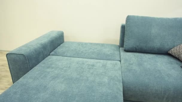 Blue sofa with textile upholstery is laid out in comfortable place to sleep