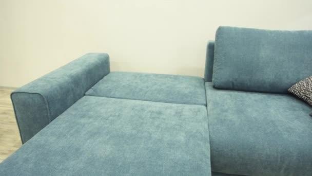 Modrá pohovka s textilním čalouněním je umístěna na pohodlném místě k přespání