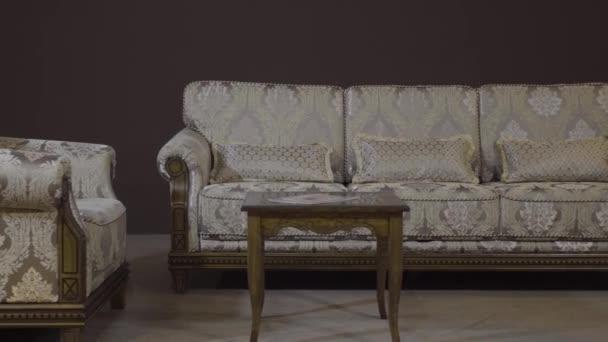 Pohovka s textilním čalouněním, židlí a konferenčním stolkem s vyřezávanýma dřevěnýma nohama