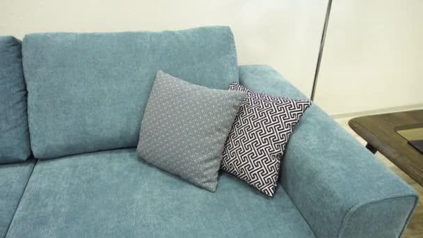 Decorative gray designer pillows of eco-friendly materials lie on blue sofa