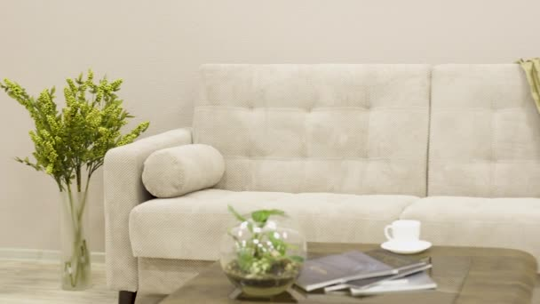 Minimalistická bílá textilní pohovka s designovým křeslem a dekorativním kostkovaným