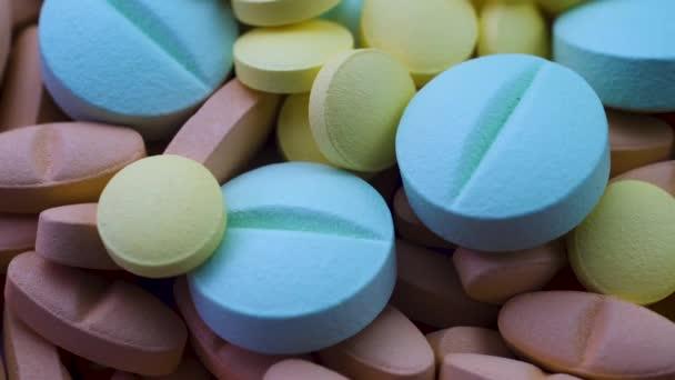 Kulaté modré a žluté antivirové pilulky leží na červených antibiotikách. Otočení zblízka