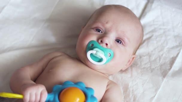 batole leží na plence s hračkou v ruce a snaží se ji okousat