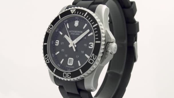 Ibach, Switzerland 7.04.2020 - Victorinox Man watch stainless steel case black clock face dial rubber strap rotating on stand close up isolated on white background