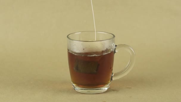 fekete teafilter emelés és csepp üveg átlátszó bögre főzni tea izolált bézs háttér lassított felvétel közeli