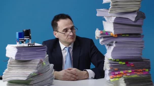 Úředník sedí u stolu se dvěma velkými hromadami papírů a zvedá hlavu.
