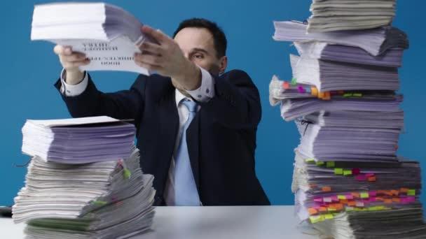 Úředník ve středním věku přesouvá na stůl hromádky papírů. Izolované modré pozadí.