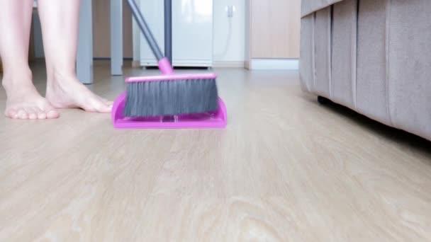 Žena úklid zametání podlahy v kuchyni štětcem a popelnice