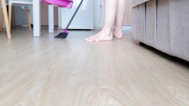 Frau putzt mit Pinsel und Kehrschaufel den Küchenboden