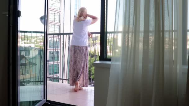 Blond žena v dlouhých šatech stojící na balkóně, dívající se do dálky, dotýkající se jejích vlasů a relaxační, pohled zevnitř místnosti otevřenými dveřmi, letní den