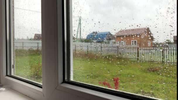 Dešťové kapky stékající po skle venkovského okna, letní déšť, zatažená šedá obloha, smutek a osamělost