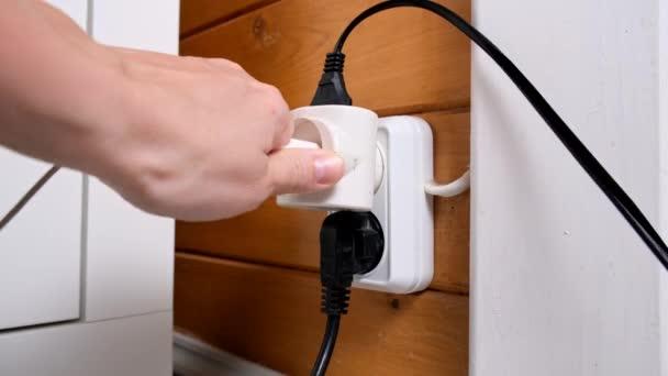 A kéz dugó és húzza ki a konnektor a konnektorba, túlterhelt kimenet kiterjesztéssel és sok aljzat csatlakoztatva, a tűz és rövidzárlat kockázata egy faházban