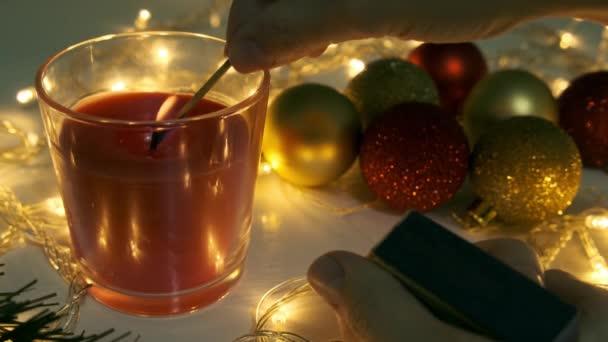 Ruka zapalování červené vánoční svíčky, hořící svíčka oheň na stole s vánoční girland a borovice dekorace a míče