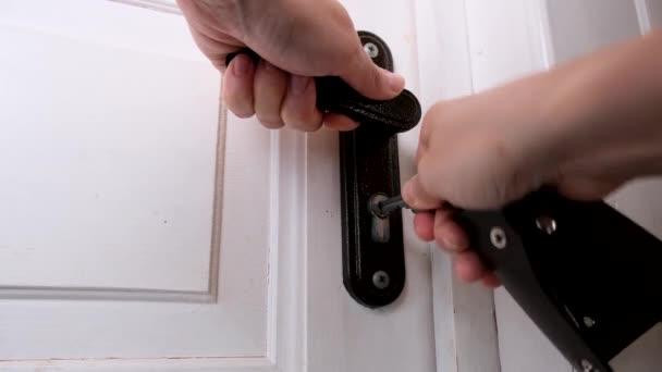 Ruka, která se snaží zapadnout, zasune klíč do klíčové dírky a otočí jím, aby zamkla bílé dřevěné dveře, koncepci domácí bezpečnosti a ochrany