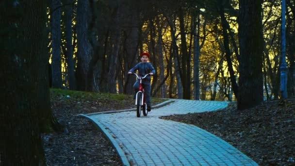 Malého chlapce jedoucího na kole v parku, park v západu slunce, pomalý pohyb