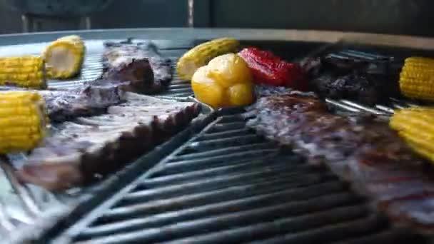 Jehněčí žebra a zelenina na rotující gril, maso a kukuřice na grilu, 4k